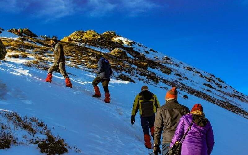 Trekkers climbing the Kedarkantha Peak